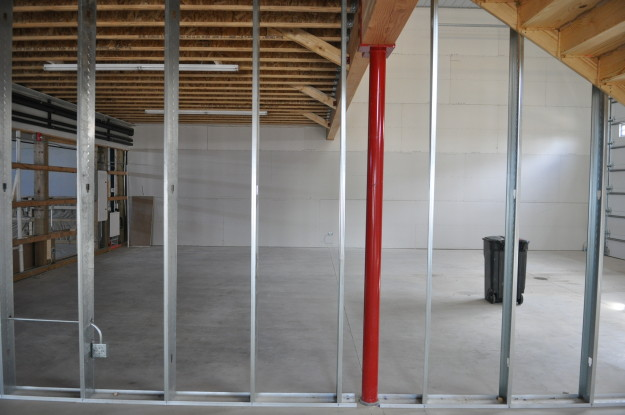 iron gate motor condos red pole under construction support beams wood work flooring ceiling
